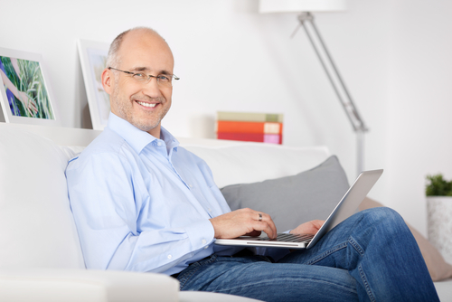 man sitting on couch with laptop in his lap